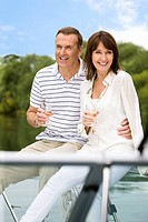 Couple sitting on boat drinking