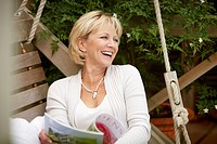 Smiling woman reading magazine