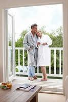 Couple in bathrobes drinking coffee on balcony