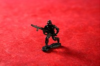plastic toy soldier over red