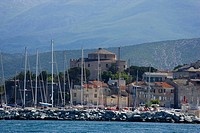 France, Corsica. Mast of boats and breakwater below citadel and other buildings of St. Florent.
