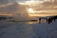 Iceland, Geysir. Tourists looking at steam coming from geyser in the snow.