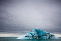 Norway, Svalbard, Nordaustlandet, Deep blue iceberg floating near face of Brasvellbreen Icefield on stormy summer morning