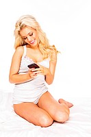 blond woman sending a text message using smartphone lying down on bed