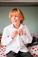 Young boy doing up the buttons of his school shirt while sitting on his bed