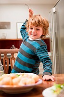 Young boy with fork raised about to stab potato