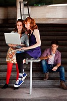 Two young woman looking at a laptop at the bottom of steps