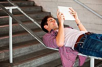 Young man using a digital tablet while lying on a railing