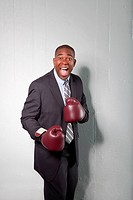 Mature businessman wearing boxing gloves, smiling