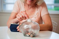 Senior woman saving money in piggy bank