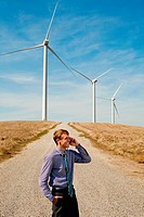 Man using mobile phone in front of wind turbines