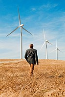 Man walking in front of wind turbines