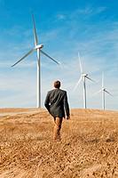 Man walking in front of wind turbines