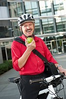 Germany, Bavaria, Mature man on bicycle with fruit, portrait, smiling