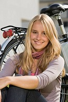 Germany, Bavaria, Teenage girl sitting by bicycle, smiling, portrait