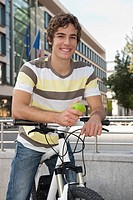 Germany, Bavaria, Young man on bicycle with apple, smiling, portrait