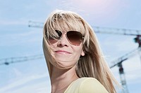 Germany, Cologne, Young woman with sunglasses, smiling