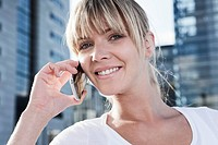 Germany, Cologne, Young woman using cell phone, portrait