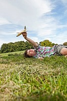 Germany, Bavaria, Boy playing with model airplane in park