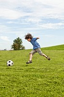 Germany, Bavaria, Boy playing with soccer ball in park