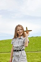 Germany, Bavaria, Girl playing with model airplane in park, smiling, portrait