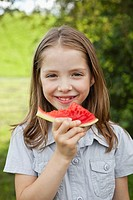 Germany, Bavaria, Girl eating watermelon in park, smiling, portrait