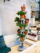 Flower pots on a decoration display stand in Bourdeilles, Dordogne, France