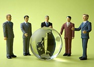 Miniature businessmen surrounding glass globe