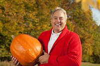 Germany, Bavaria, Mature man holding pumpkin, smiling, portrait