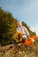 Germany, Bavaria, Girl sitting on pumpkin with leaves, smiling, portrait