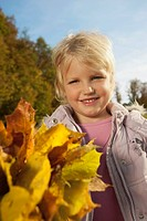 Germany, Bavaria, Girl holding leaves, smiling, portrait