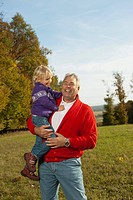 Germany, Bavaria, Grandfather carrying granddaughter, smiling
