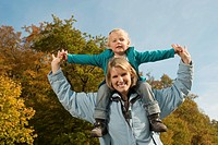 Germany, Bavaria, Mother carrying daughter on shoulder, smiling