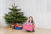 Germany, Munich, Girl holding present near christmas tree, smiling, portrait