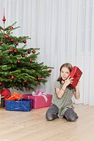 Germany, Munich, Girl holding present near christmas tree