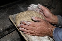 Germany, Upper Bavaria, Egling, Senior man baking bread in wood stove bakery, close up