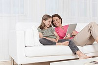 Germany, Munich, Mother and daughter using digital tablet, smiling