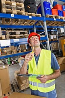 Germany, Bavaria, Munich, Manual worker with clipboard in warehouse