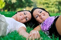 Togetherness _ two smiling sisters lying in grass outdoors and holding hands