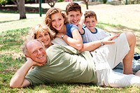 Three generation Caucasian family lying on green grass in the park smiling.