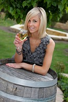 beautiful young woman with glass of wine standing at wine cask