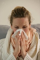 A blonde woman wiping her nose as she suffers from common cold