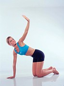 Young adult woman with the doing sports _ legs stretch _ to lift upright kneeling position and an arm