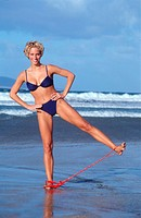 woman does doing sports at the beach with elastic band