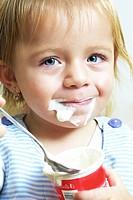 Small child eats a yogurt