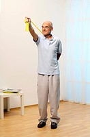 older man is training his upper arm with a stretch_band _ muscularity _ senior