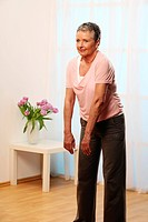older woman doing gymnastics fŸr the shoulders _ senior is doing exercise fŸr the back _ less pain _ mooving the shoulders to the back and to the fron...