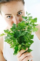 young woman holding a bunch of lovage in her hands and is taking a smell on it