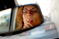 Young woman paints her lips in her car