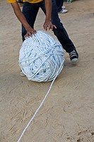 Boy rolling a giant ball of string